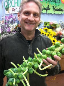 My husband holding a brussel sprout stalk